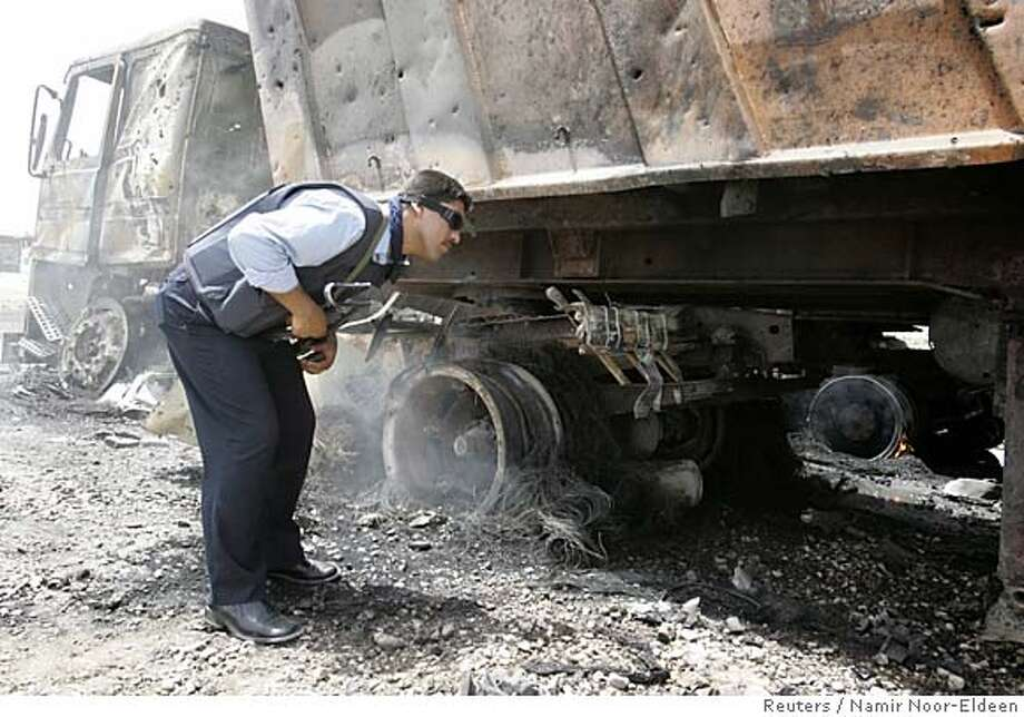 An Iraqi policeman inspects a burnt truck after a bomb attack near the airport in Baghdad Photo: NAMIR NOOR-ELDEEN