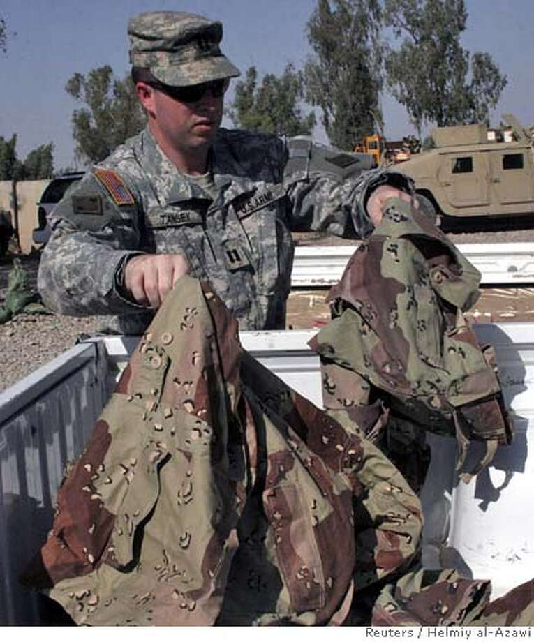 US soldier holds army uniforms of the 36 gunmen arrested in Baquba Photo: HELMIY AL AZAWI