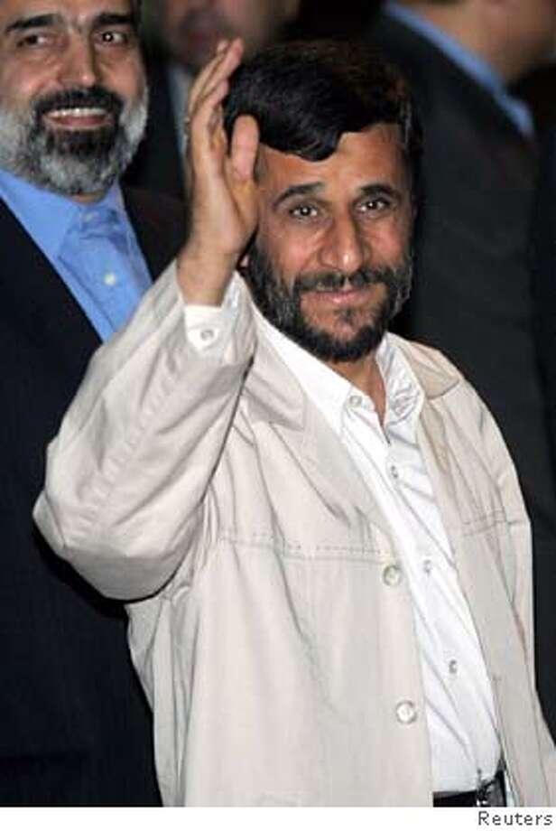 President of Iran Mahmoud Ahmadinejad waves to journalists after he arrive at Halim Perdanakusumah airport in Jakarta