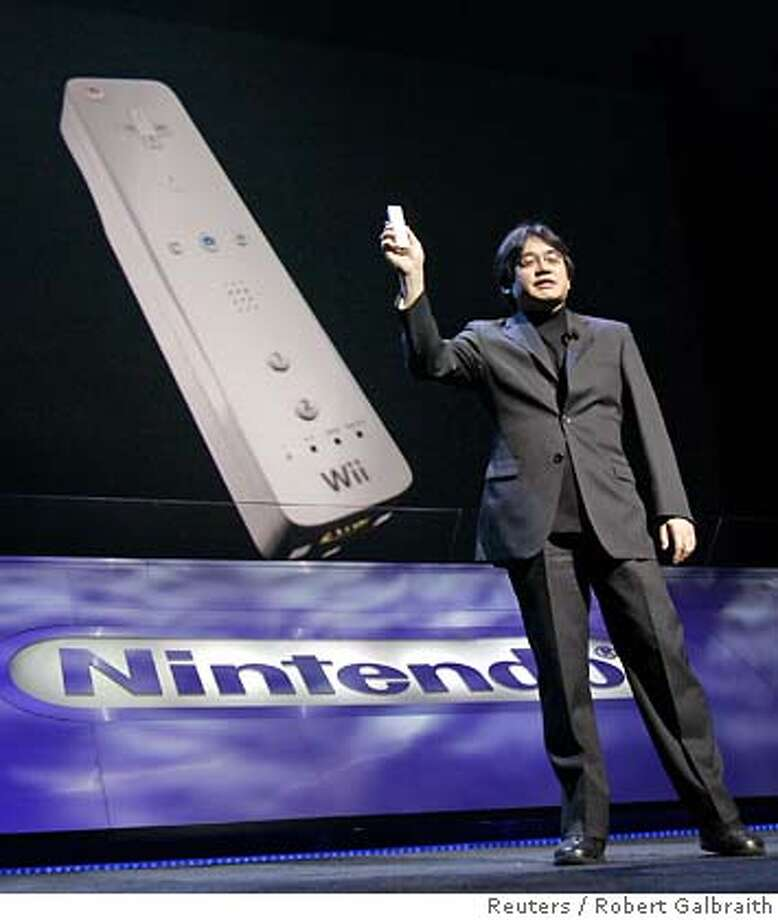 "Satoru Iwata, president of Nintendo, displays the new ""Wii"" remote control device during the Electronic Entertainment Expo in Hollywood, California May 9, 2006. The device is used with the new Wii home console, which permits users to manipulate action on their television screens through the life-like motion of the Wii remote. REUTERS/Robert Galbraith 0 Photo: ROBERT GALBRAITH"