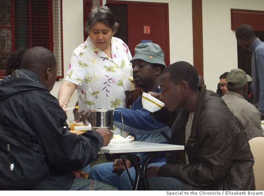 NOTE: FREELANCE PHOTO, CAPTION INCOMPLETE. WILL BE UPDATED SATURDAY 5/6/06 Bakari Coulibali (center, floppy hat) having breakfast at the Saint hippolyte Roman Catholic Church in Paris... PHOTO CREDIT: Elizabeth Bryant/Special to the Chronicle.