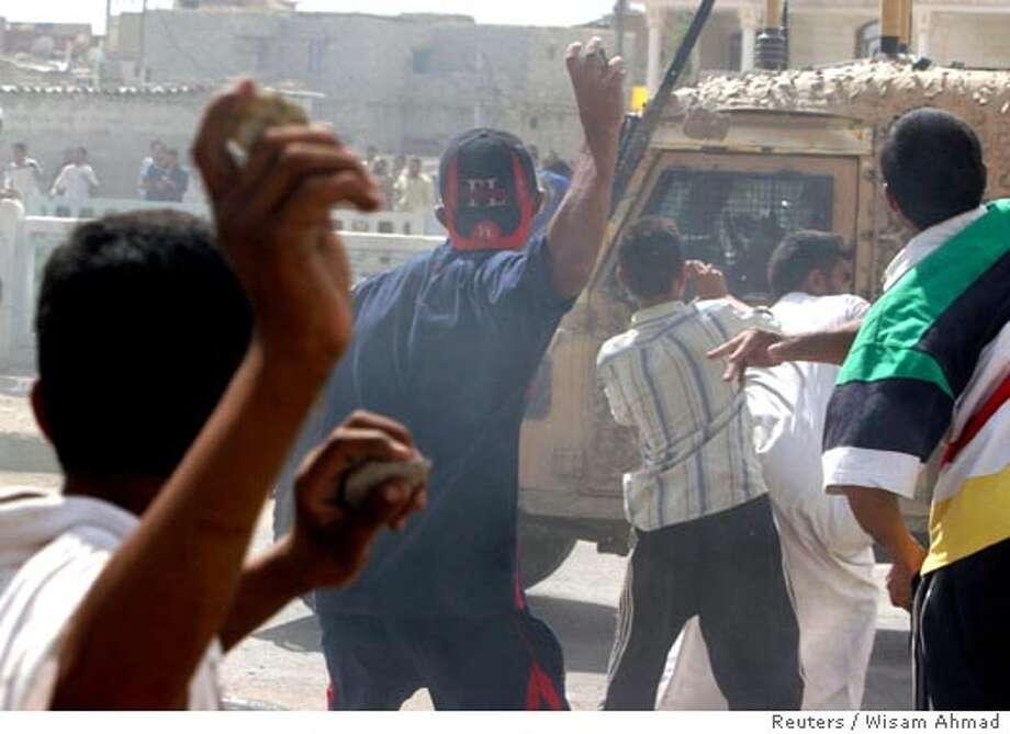 Iraqi residents throw stones at passing British armoured vehicle near British helicopter crash site in Basra Photo: STRINGER/IRAQ