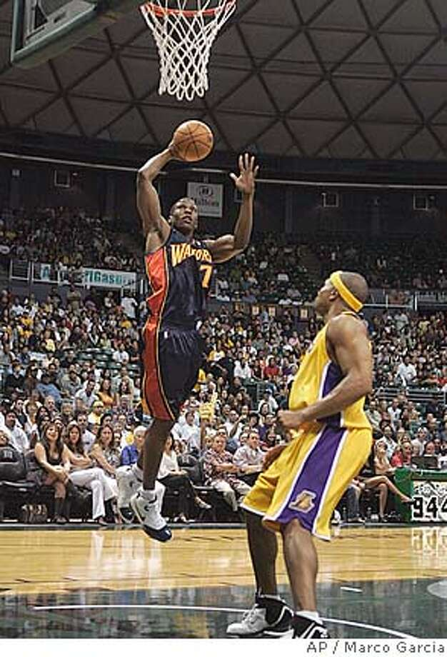 Golden State Warriors guard Kelenna Azubuike dunks over Los Angeles Lakers guard Derek Fisher during the first quarter of their basketball exhibition game at the Stan Sheriff Center, Tuesday, Oct. 9, 2007 in Honolulu. (AP Photo/Marco Garcia) Photo: Marco Garcia