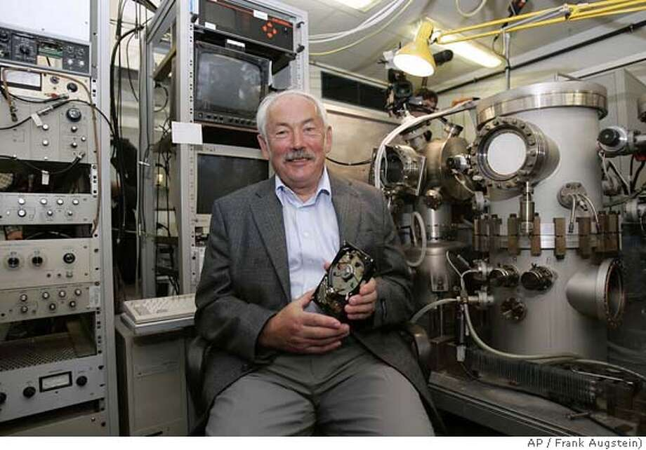 Physic Nobel Prize winner Peter Gruenberg sits in his laboratory at the Juelich research center in Juelich, western Germany, during a meeting with the media on Tuesday, Oct. 9, 2007. France's Albert Fert and German Peter Gruenberg won the 2007 Nobel Prize in physics on Tuesday for a discovery that has shrunk the size of hard disks found in computers, iPods and other digital devices. (AP Photo/Frank Augstein) Photo: FRANK AUGSTEIN