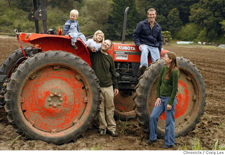 ORGANIC03_1339_cl.JPG  Story on organic farms. This is Blue Moon Organics in Aptos owned by Patrick DeYoung and Greg Rawlings. Photo of Greg Rawlings (3rd from left), his wife, Amy Rawlings (far right), Patrick DeYoung (2nd from right on top of the wheel), and Greg and Amy's two children, Malia, 4 (2nd from left) and Roen, 20 months-old (far left). Craig Lee / The Chronicle MANDATORY CREDIT FOR PHOTOG AND SF CHRONICLE/ -MAGS OUT Photo: Craig Lee
