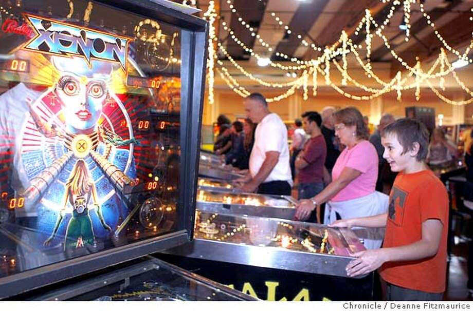 pinball_058_df.jpg  Calvin Murphy, 11, (orange t-shirt) from Concord, plays pinball. The Pacific Pinball Exposition was held at the Exhibition Hall at Marin County Civic Center. Photographed in San Rafael on 10/6/07. Deanne Fitzmaurice / The Chronicle Photo: Deanne Fitzmaurice