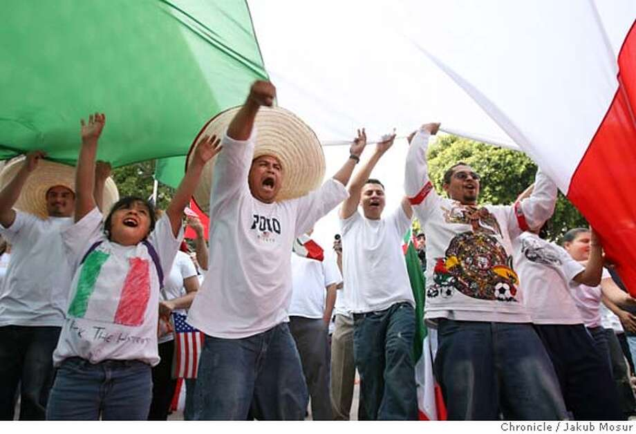 Immigration_LA_18_JMM.JPG Demonstrators cheer underneath a giant Mexican flag near the Los Angeles City Hall building during the immigrant demonstration in Los Angeles. The demonstrators are skipping work and school today as part of a large cross country boycott of work, school and shopping. Event on 5/1/06 in Los Angeles. JAKUB MOSUR / The Chronicle MANDATORY CREDIT FOR PHOTOG AND SF CHRONICLE/ -MAGS OUT Photo: JAKUB MOSUR