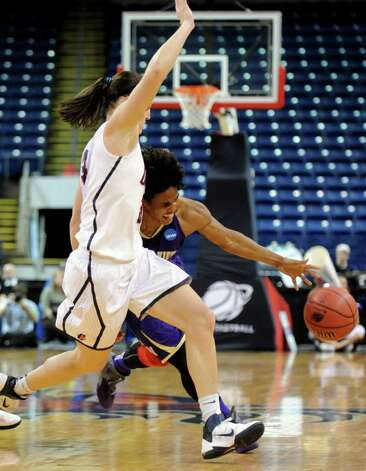 Prairie View's Latia Williams drives the ball down the court as Connecticut's Kelly Faris defends during the first-round NCAA game at the Webster Bank Arena in Bridgeport, Conn. Saturday, Mar. 17, 2012. Photo: Autumn Driscoll / Connecticut Post