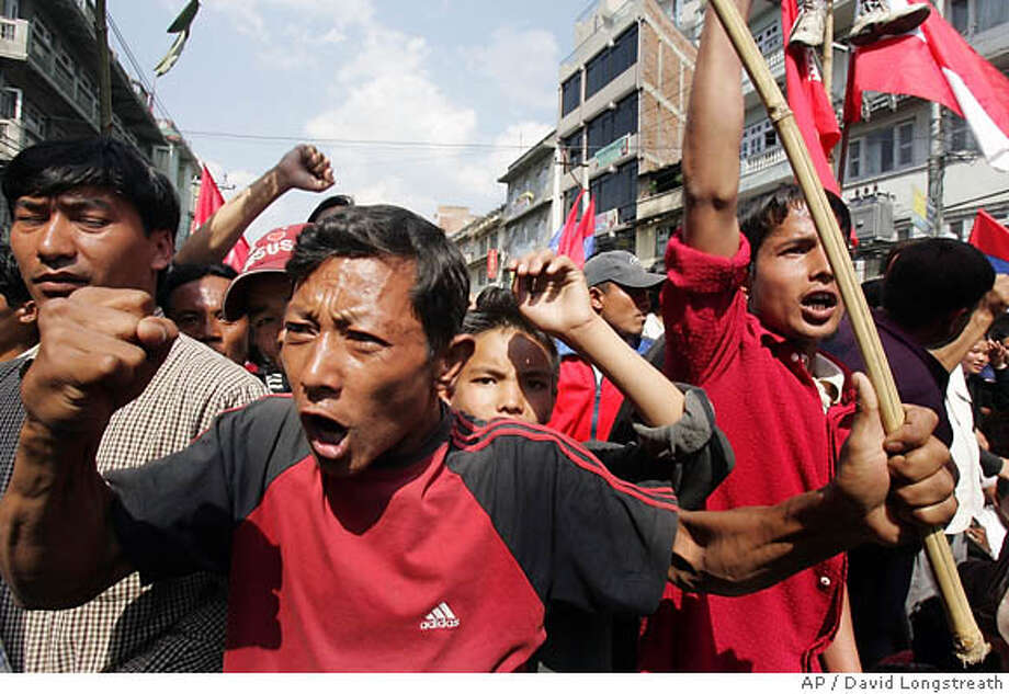 Demonstrators gather on the outskirts of Katmandu Monday, April 24, 2006, to shout anti-Royalist slogans. Nepal's capital begins its fifth consecutive day under curfew Monday, as opposition parties planned a massive rally to demand an end to King Gyanendra's rule and a new constitution. The 11 a.m.-6 p.m. curfew imposed in Katmandu and Lalitpur, a major suburb of the city, follows nearly three weeks of demonstrations in which police and anti-monarchy protesters have frequently clashed in the capital. On Monday, the U.S. State Dept. ordered all non-emergency embassy staff and family members to leave Nepal, according to an embassy spokesman, Robert Hugins. He said about half of the staff would leave. (AP Photo/David Longstreath) Photo: DAVID LONGSTREATH