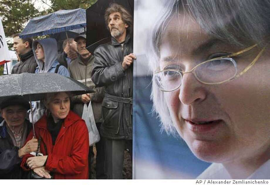 People stand near a portrait of Anna Politkovskaya during a rally to mark the first anniversary of the Russian journalist's slaying, Moscow, Sunday, Oct. 7, 2007. Politkovskaya's death _ in an execution-style slaying in the entryway of her Moscow apartment building _ resonated worldwide, casting a harsh light on the state of civil society and the safety of journalists and government critics under President Vladimir Putin. (AP Photo/Alexander Zemlianichenko) Photo: ALEXANDER ZEMLIANICHENKO