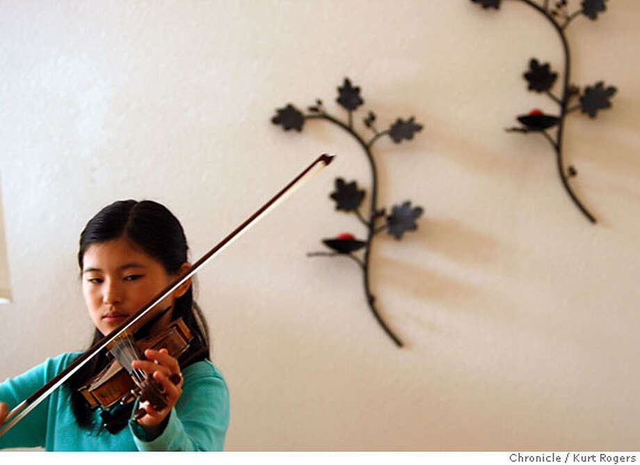 Mindy Chen an 11 year old violin whiz . tunes her violin in the living room of her fremont home.  PRODIGY_016_KR.JPG FREMONT, CA, on Friday, September, 21. photo taken: 9/21/07  KURT ROGERS / The Chronicle * Ran on: 10-07-2007  Mindy Chen, an 11-year-old from Fremont, practices the violin at home. Photo: Rogers, Kurt