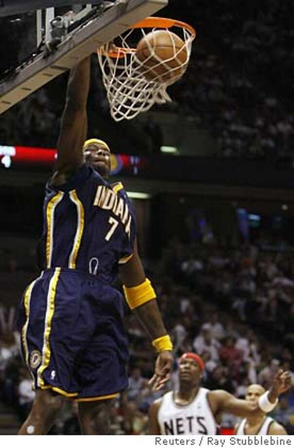 Indiana Pacers O'Neal stuffs in front of New Jersey Nets Robinson in East Rutherford Photo: RAY STUBBLEBINE