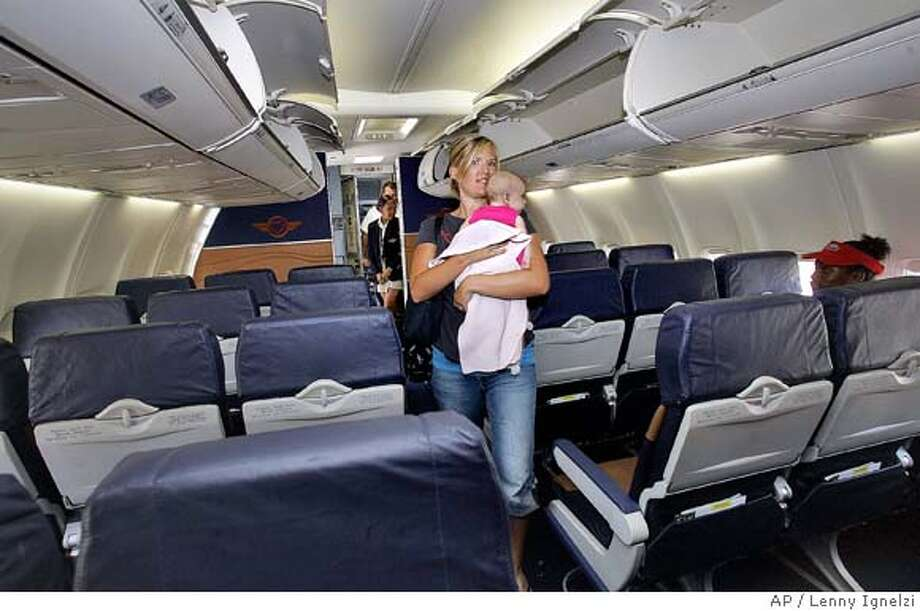 Katie Seat carries her three-month-old daughter, Syndnee, as she looks for her assigned seat after boarding Southwest Airlines flight 2444 from San Diego to Phoenix Monday, July 10, 2006, in San Diego. The airlines used the single flight as an experiment to see if assigned seats would interfere with their scheduling. (AP Photo/Lenny Ignelzi)  Ran on: 07-16-2006 Photo: LENNY IGNELZI