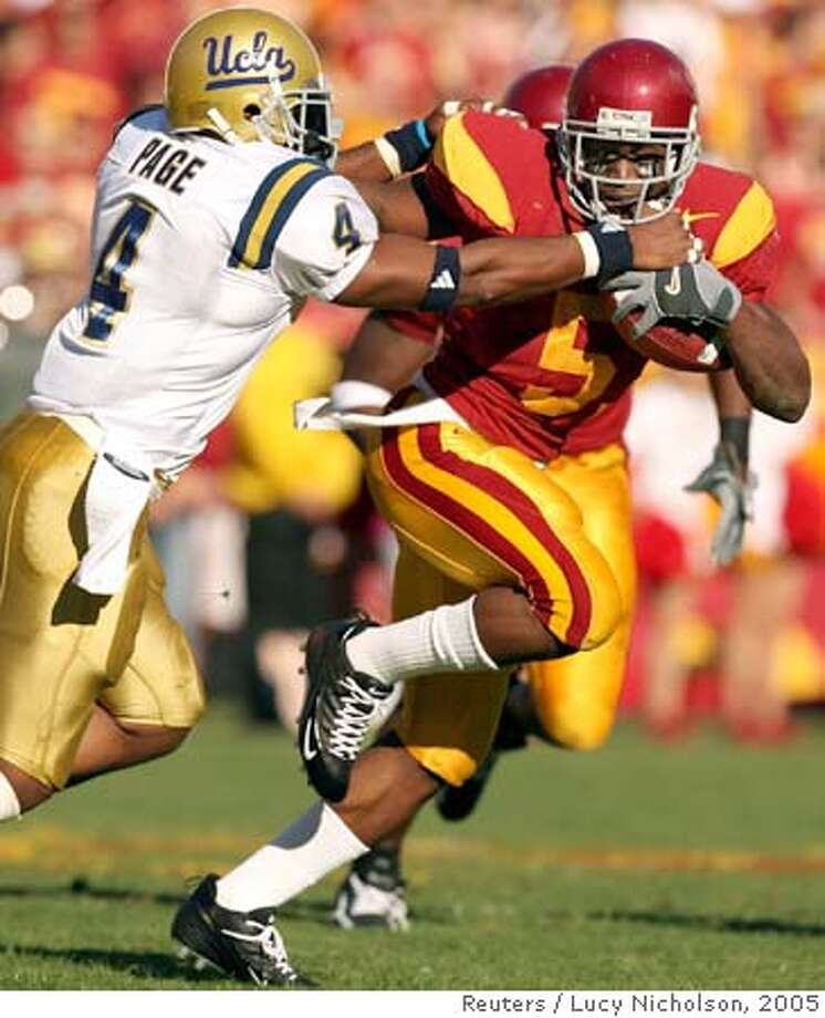 University of Southern California tailback Reggie Bush breaks a tackle from UCLA's Jarrad Page during the first quarter of their NCAA game in Los Angeles Photo: LUCY NICHOLSON