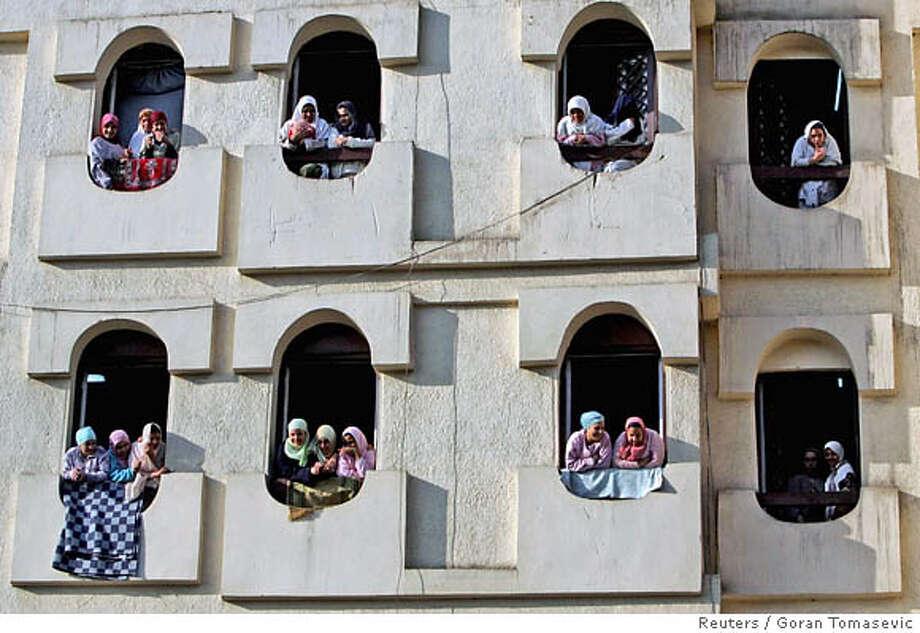 Egyptian women watch a parade in Cairo Photo: GORAN TOMASEVIC