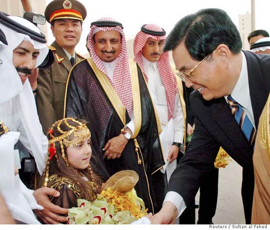 Chinese President Hu is greeted by Saudi girl dressed in traditional outfit in Riyadh Photo: STR