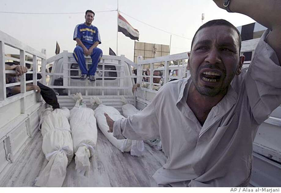 An Iraqi man reacts as four victims of a U.S raid lie on a pick-up truck, at a cemetery in Najaf, 160 kilometers (100 miles) south of Baghdad, Iraq, on Friday, Oct. 5, 2007. U.S. forces backed by attack aircraft killed at least 25 Shiite militia fighters north of Baghdad Friday in an operation targeting a cell accused of smuggling weapons from Iran, the military said. (AP Photo/Alaa al-Marjani) Photo: ALAA AL-MARJANI