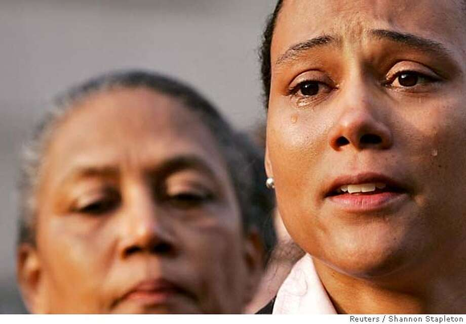 REFILE - ADDING IDENTITY OF WOMAN AT LEFT Marion Jones sheds tears as she speaks to the media after leaving the U.S. Federal Courthouse in White Plains, New York October 5, 2007. Jones pleaded guilty on Friday to lying to federal investigators and admitted to using steroids, which could cost her the five medals she won in the 2000 Sydney Olympics. At left is Jones' mother, Marion Toller. REUTERS/Shannon Stapleton (UNITED STATES) 0 Photo: SHANNON STAPLETON