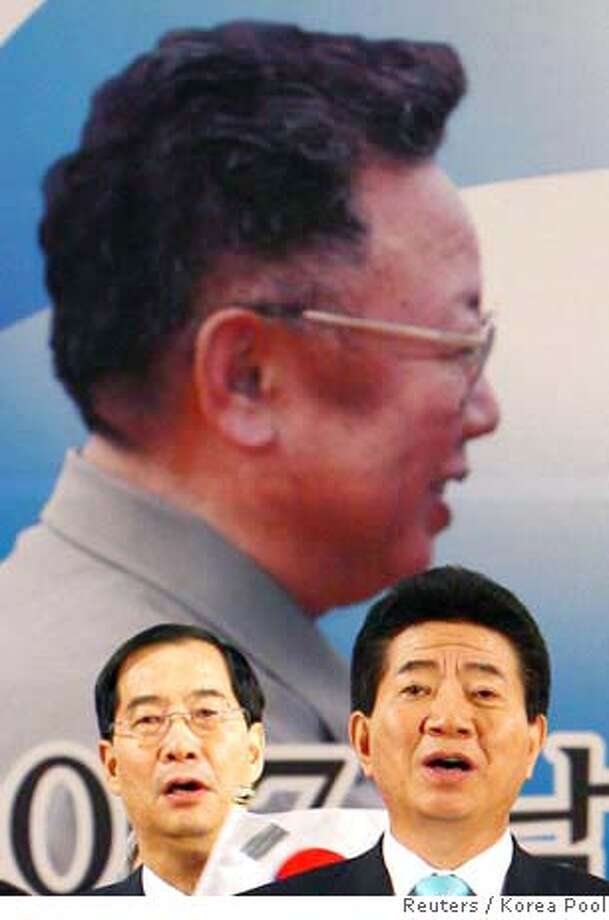 South Korea's Prime Minister Han Duck-soo (L) and President Roh Moo-hyun sing a song about the unification of Korea at a welcoming ceremony after arriving at the South Korean Customs, Immigration and Quarantine (CIQ) near the Demilitarized Zone in Paju, north of Seoul, October 4, 2007. The leaders of North and South Korea pledged on Thursday to bring peace to the Cold War's last frontier by seeking talks with China and the United States to formally end the 1950-1953 Korean War. REUTERS/Korea Pool (NORTH KOREA) KOREA OUT. EDITORIAL USE ONLY. NOT FOR SALE FOR MARKETING OR ADVERTISING CAMPAIGNS.  Ran on: 10-05-2007  South Korea Prime Minister Han Duck Soo (left) and President Roh Moo Hyun sing about unification at a welcoming ceremony. Photo: POOL