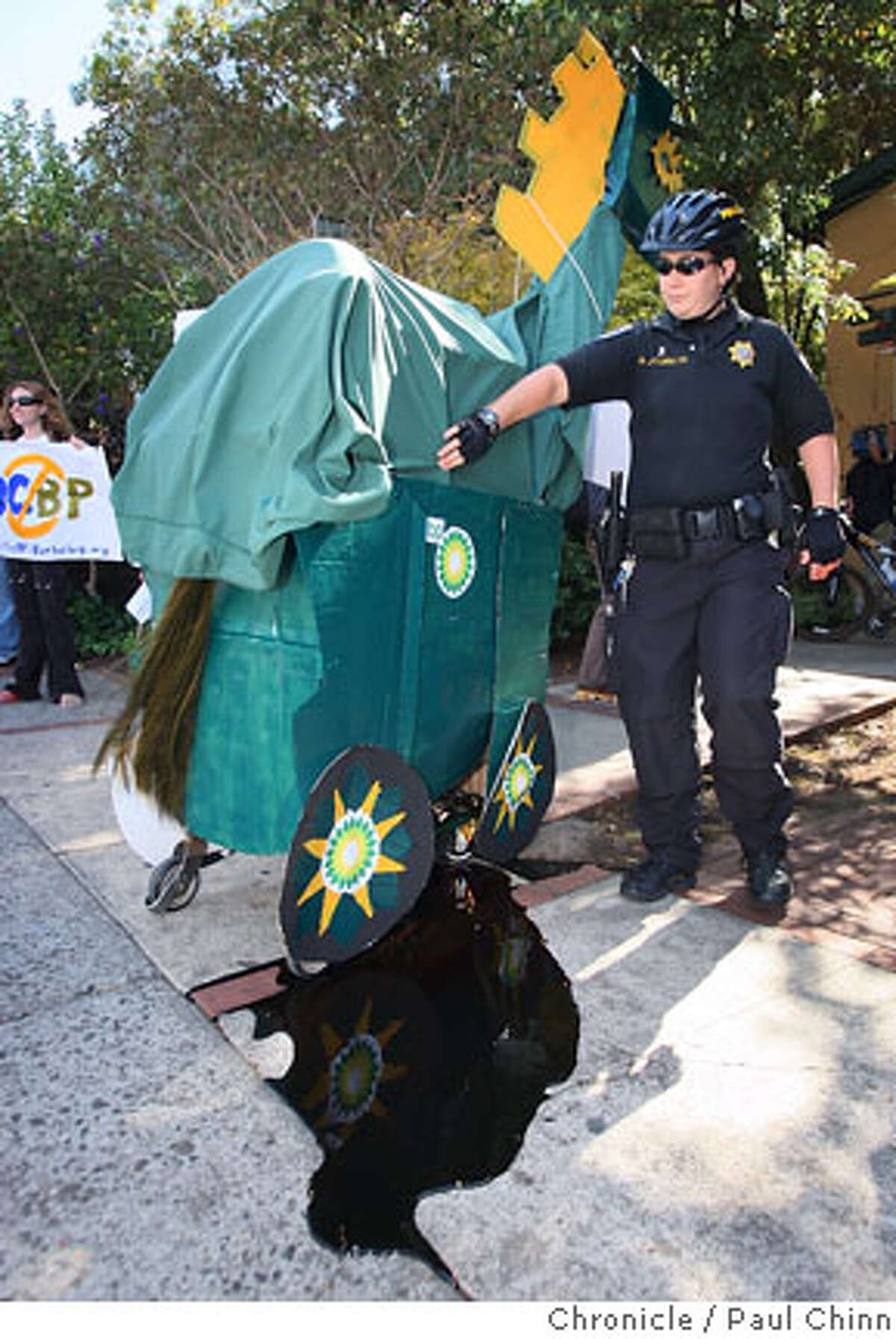A UC police officer moves in tend to a Trojan Horse, delivered by protesters, that was dripping an oil-like fluid (it was molasses) in front of the Bancroft Hotel where a biofuel conference was convening in Berkeley, Calif. on Thursday, Oct. 4, 2007. The demonstration was organized to denounce the university's $500 million deal with oil giant BP and was timed to coincide with the two-day conference. PAUL CHINN/The Chronicle