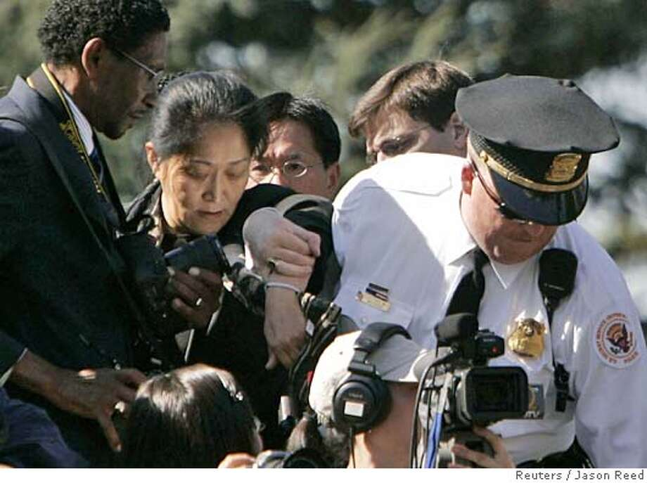A uniformed secret service agent ejects a protester from a welcoming ceremony for Chinese President Hu Jintao hosted by U.S. President George W. Bush on the South Lawn of the White House Washington, April 20, 2006. REUTERS/Jason ReedRan on: 04-21-2006  A uniformed guard removes Falun Gong heckler Wang Wenyi from the welcoming ceremony for Chinese President Hu Jintao. Photo: JASON REED