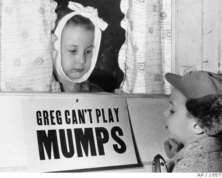 **FILE** A Jan. 16, 1957 file photo shows Greg Cox, left, 7, in Altamont, Ill., as he looks at his friend Jon Douglas, 6, through the doorway while he recovers from mumps. In the worst outbreak in more than 20 years, mumps cases are spilling out of Iowa, popping up in at least nine other Midwestern states. Cases have also turned up in Illinois, Kansas, Minnesota, Missouri, Nebraska, Oklahoma and Wisconsin. Greg's parents posted the sign but it didn't working out too well because most of Greg's playmates were too young to read. (AP Photo, File) JAN. 16, 1957 FILE PHOTO. BLACK AND WHITE ONLY. Photo: X
