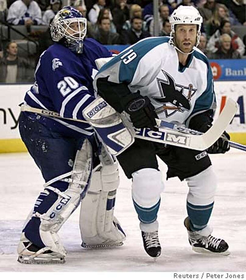 San Jose Sharks Joe Thornton bumps Toronto Maple Leafs goaltender Ed Belfour Photo: PETER JONES