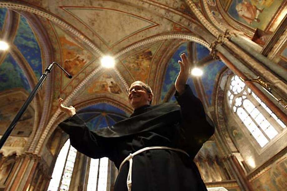 The Rev. Vincenzo Coli of the Basilica of St. Francis of Assisi unveils 13th century frescoes restored after damage from the 1997 quake. Associated Press photo by Alessandra Tarantino