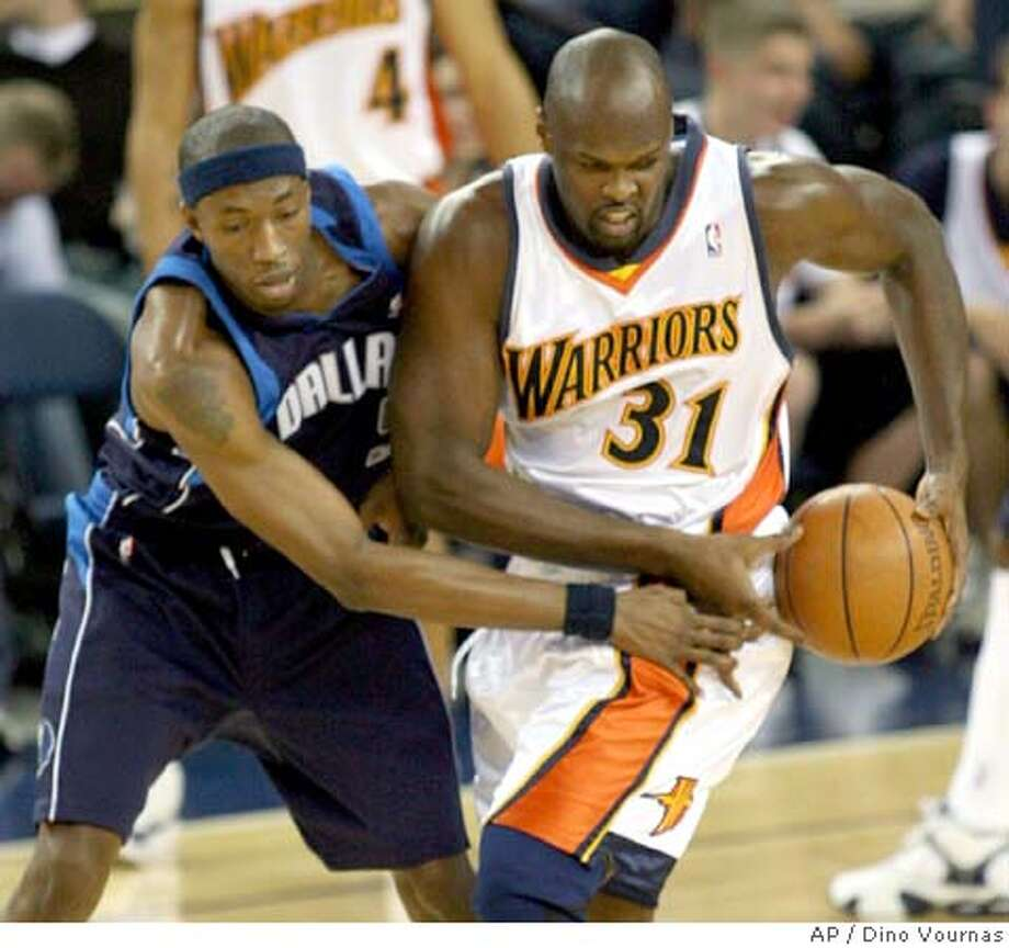 Dallas Mavericks' Josh Howard, left, guards Golden State Warriors' Adonal Foyle during the first quarter of an NBA basketball game Wednesday, April 12, 2006, in Oakland, Calif. (AP Photo/Dino Vournas) EFE OUT Photo: DINO VOURNAS