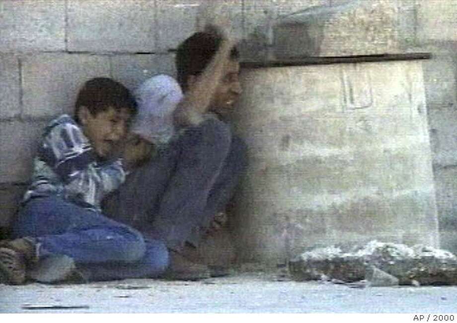 ** FILE ** In this image from television, Jamal Al-Dura signals his position while protecting his 12-year-old son Mohammed Jamal, as they shelter behind a barrel from crossfire in this Saturday, Sept. 30, 2000, file photo near Netzarim Jewish settlement in the southern Gaza City. Israel has accused a French TV network of manipulating footage to make Israel look responsible for the September 2000 shooting death of a 12-year-old Palestinian boy.The claims, made by a senior government official, go further than an official army investigation into the incident, and were rejected by the network, France 2. The army probe said it was highly unlikely that troops shot the boy, but did not rule out the possibility altogether or make any accusations against the French network. (AP PHOTO/FRANCE 2, file) ** NO SALES: TV OUT: FRANCE OUT: ** Photo: Associated Press