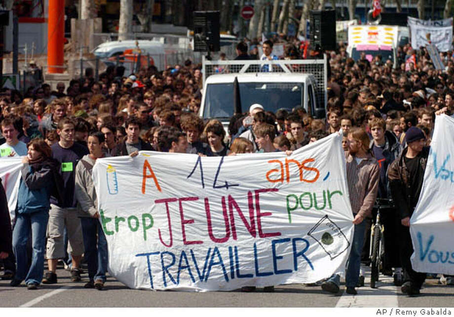 People demonstrate in Toulouse, southwestern France, Tuesday April 11, 2006, as they are seemingly emboldened by President Jacques Chirac's cave-in on a youth jobs measure, and they try to get rid of other government labor reforms. Unions declared victory on Monday after Chirac abandoned the measure that had spurred nationwide unrest, paralyzed secondary schools and universities and created a crisis for the government. Banner reads: Too young to work at 14 years old. (AP Photo/Remy Gabalda) Photo: REMY GABALDA