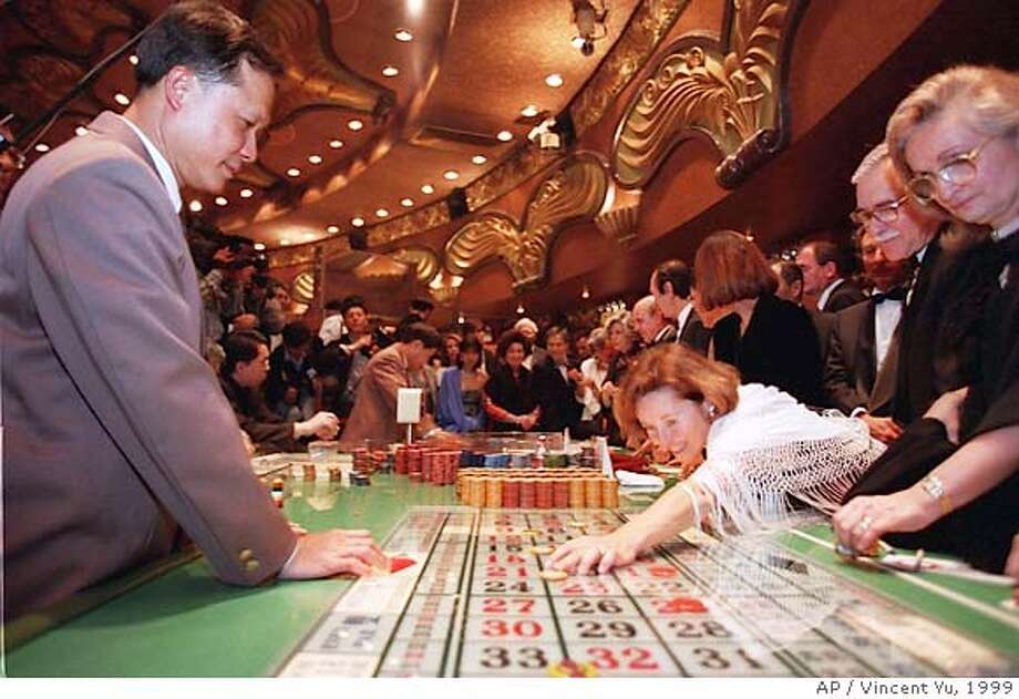 FILE--A woman places a bet on the roulette table at Casino Lisboa, the most famous and popular club in Macau, Feb. 15, 1999. Stanley Ho, the tycoon who has controlled Macau's lucrative casino trade since 1962, will be stripped of his monopoly next year, opening the way for competition in the tiny gambling haven, a Hong Kong newspaper reported Tuesday. (AP Photo/Vincent Yu/file) Ran on: 06-13-2004  Iberian flavor at Igreja de Sao Domingo (Church of St. Dominick). Ran on: 11-12-2004  A woman placed a bet on the roulette table five years ago at Casino Lisboa in Macau, formerly a Portuguese colony. Photo: VINCENT YU