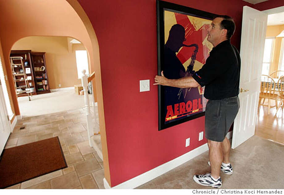 """CHRISTINA KOCI HERNANDEZ/CHRONICLE  President of """"Quake Hold"""", Dean Reese, checks the stability of a large piece of art. Story is about """"deadly decor"""" - tips on decorating a home so it's stylish AND safe in the event of an earthquake. We photograph one condo and one home. This is the home belonging to Mary Jo Townzan. She has kids and hired , an """"interior mitigation specialist"""" to make her home quake-safe - securing furniture, valuables, etc. Photo: CHRISTINA KOCI HERNANDEZ"""