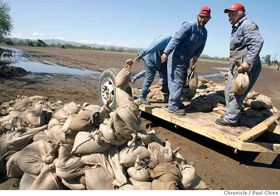 Local farmers worried about a breach in the levees unload a pile of sandbags at a staging area near the confluence of the San Joaquin and Stanislaus Rivers. San Joaquin County officials and local residents took advantage of a break in the rainstorms to shore up the fragile levee system near Vernalis, CA on 4/13/06.  PAUL CHINN/The Chronicle MANDATORY CREDIT FOR PHOTOG AND S.F. CHRONICLE/ - MAGS OUT Photo: PAUL CHINN