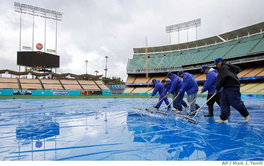 Ground crew members push water off the tarp at Dodger Stadium prior to the Los Angeles Dodgers' baseball game against the San Francisco Giants, Friday night, April 14, 2006, in Los Angeles. (AP Photo/Mark J. Terrill) Photo: MARK J. TERRILL