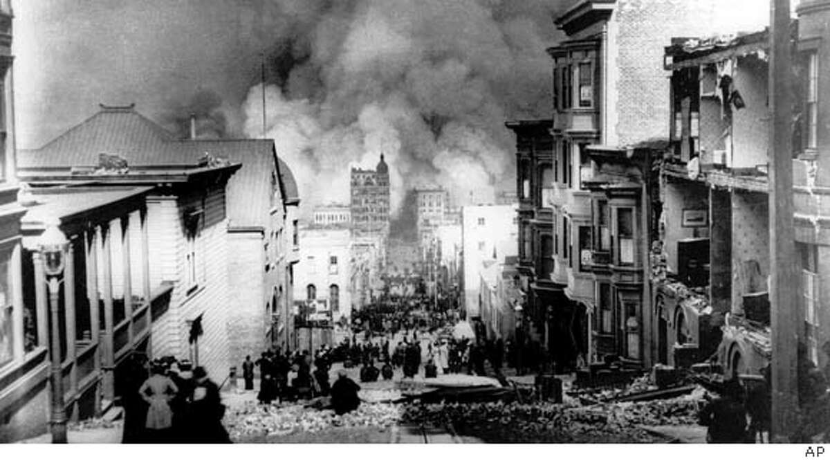 After the 1906 quake, people on Sacramento Street are awestruck by the enormity of the devastation and the resulting fires in San Francisco. Photo by Arnold Genthe, 1906
