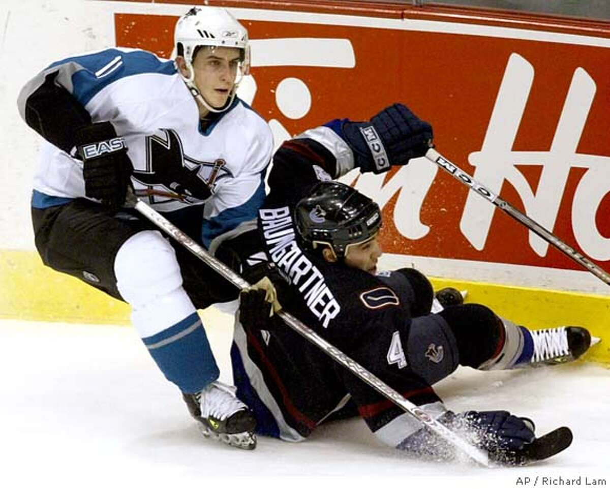 Vancouver Canucks' Nolan Baumgartner (4) crashes into the end boards after being taken out by San Jose Sharks Marcel Goc during the first period of NHL hockey action in Vancouver, Wednesday, April 12, 2006. (AP PHOTO/CP, Richard Lam)