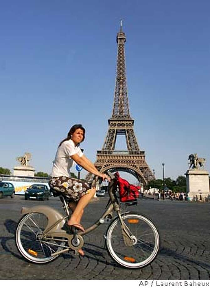 A rider uses a new bicycle provided by Paris City Hall, around the Eiffel Tower in Paris, Sunday, July 15, 2007. Paris City Hall launched a new bicycle service Sunday, with more than 10,600 posted at 750 stations all over the city and prices starting at a euro (US$1.36) for a one-day pass. Users can take a bike and put it back at any station around town. (AP Photo/Laurent Baheux) Photo: LAURENT BAHEUX