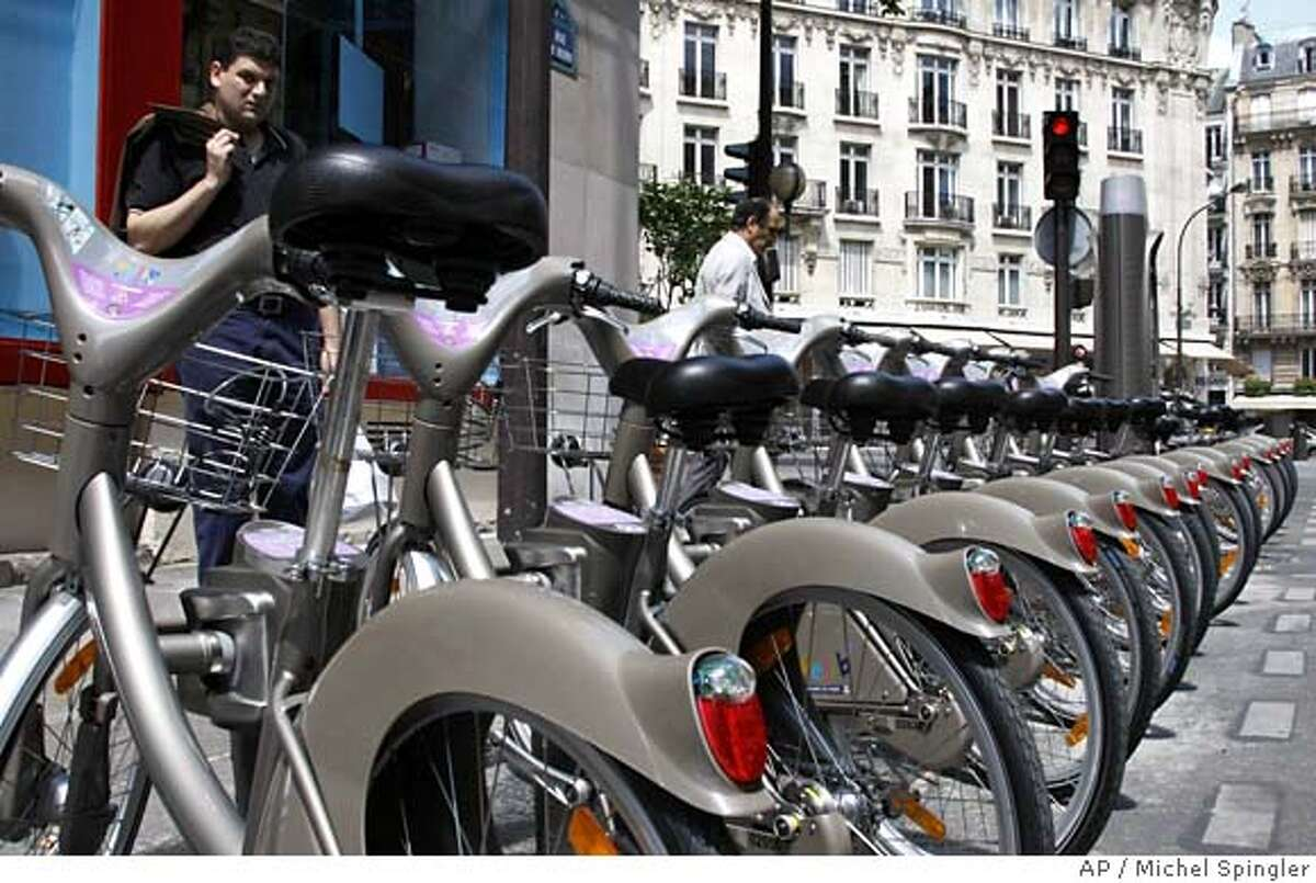 """Men examine new bicycles known as """"Velib"""" in Paris, Saturday, July 14, 2007. Starting July 15, more than 10,600 bikes will be posted all over town at 750 stations, and the numbers of both will nearly double by the year's end. The great news for tourists is that City Hall has made sure the service is convenient for tourists, not just Parisians, by offering short-term passes and access in eight languages. The idea is flexibility: You grab a bike from any station around town, they pop up every 330 yards or so, and park it at any other station. (AP Photo/Michel Spingler)"""