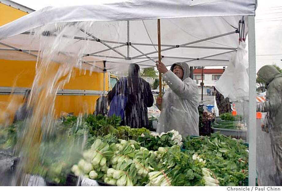 Johnny Spain used a broomstick to clear rain water from a merchant's tent. Diehard shoppers and merchants braved the elements to shop for organic produce at the Farmer's Market on Derby Street on 4/11/06 in Berkeley, CA. Many merchants say only the diehards have been shopping in the rain at the weekly market.  PAUL CHINN/The Chronicle MANDATORY CREDIT FOR PHOTOG AND S.F. CHRONICLE/ - MAGS OUT Photo: PAUL CHINN