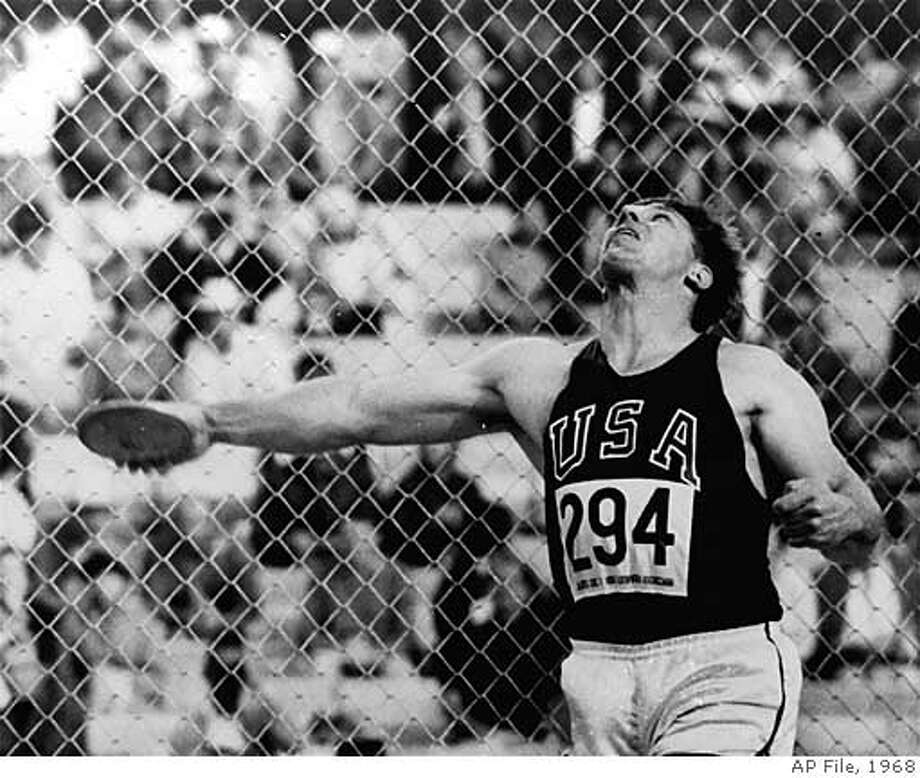 ** FILE ** Al Oerter of the United States releases the discus at the Olympic Stadium in Mexico City during the 1968 Summer Games. His throw of 212 feet, 1 1/2 inches (64.78 meters) won him his fourth gold medal. (AP Photo/File)