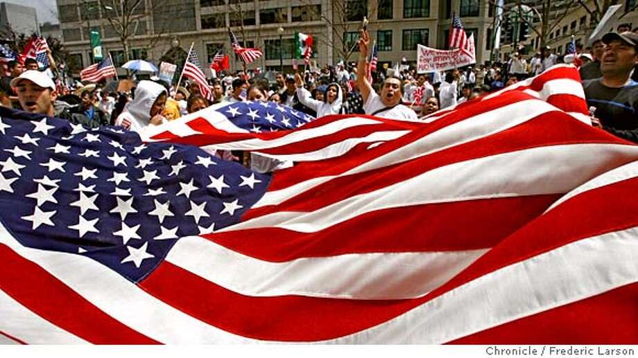 {object name} Surrounded by America flags waving in all directions thousands of protester march to the Oakland Federal Plaza for a noon day rally. Another day of immigration protests are being held in cities across the country today with tens of thousands of demonstrators expected in Oakland, San Jose, San Francisco and Berkeley. 4/10/06  Frederic Larson Photo: Frederic Larson