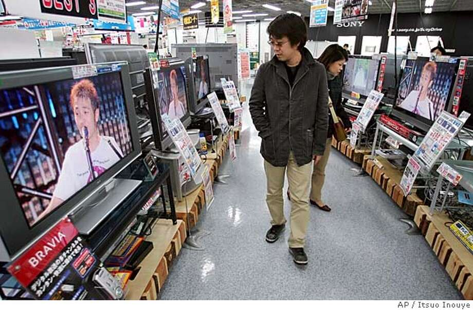 A couple checks flat panel TVs at retail chain Yodobashi Camera Co. store in Tokyo's Akihabara electronics district Wednesday, Feb. 22, 2006. Just five years ago, Japan's electronics makers were stuck in the doldrums, battered by competition from cheaper Asian rivals as prices for computer chips and gadgets nose-dived. These days, they're enjoying far brighter times. The key to the gradual turnaround at big Japan Inc. names like Panasonic, Sharp and Sony lies in one booming product: TVs. (AP Photo/Itsuo Inouye) Photo: ITSUO INOUYE