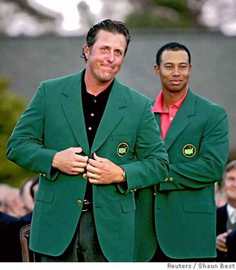 Phil Mickelson (L) of the U.S. receives green jacket from Tiger Woods (R) of the U.S. after winning the 2006 Masters golf tournament at the Augusta National Golf Club in Augusta, Georgia April 9, 2006. REUTERS/Shaun Best Photo: SHAUN BEST