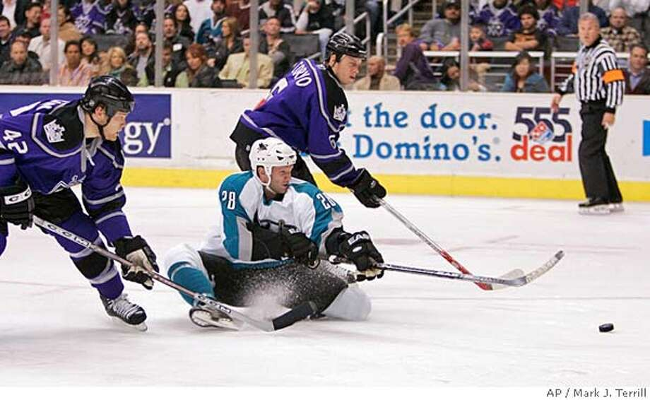 San Jose Sharks' Nils Ekman, of Sweden, takes a shot on goal as he falls to the ice, while Los Angeles Kings' Tim Gleason, left, and Joe Corvo follow during the third period of an NHL hockey game Thursday night, April 6, 2006, in Los Angeles. The Sharks won 5-0. (AP Photo/Mark J. Terrill) Photo: MARK J. TERRILL