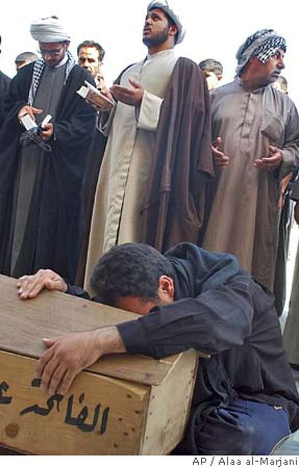 Iraqi Shiite clerics pray as a man weeps on the coffin of Jalil al-Mohammadawi, 27 who was killed in Friday's suicide attack on the Buratha mosque which killed 79 people and injured more than 160 Saturday April 8, 2006 in Najaf, 160 km (100) miles south of Baghdad, Iraq. Relatives and friends of Shiite Muslims killed in a deadly mosque attack buried their dead Saturday, carrying coffins through the streets, chanting religious rites and beating their heads and chests.(AP Photo/Alaa al-Marjani) Photo: ALAA AL-MARJANI
