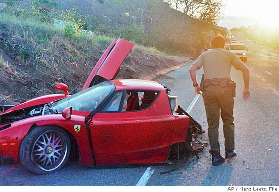 A Los Angeles County sheriff inspects the wreckage of a rare Ferrari Enzo that crashed on the Pacific Coast Highway Tuesday, Feb. 21, 2006, in Malibu, Calif. The red Ferrari, estimated to be worth more than $1 million, was going at least 100 mph when the driver lost control and struck a power pole, investigators said. Sheriff's investigators identified the owner as Stefan Ericksson, 44, of Bel Air, who escaped the wreck with only a cut lip. (AP Photo/Hanz Laetz) ** TV OUT ** EDS:FEB. 21, 2006 PHOTO ** UNITED STATES ONLY. , TV OUT. Photo: HANZ LAETZ