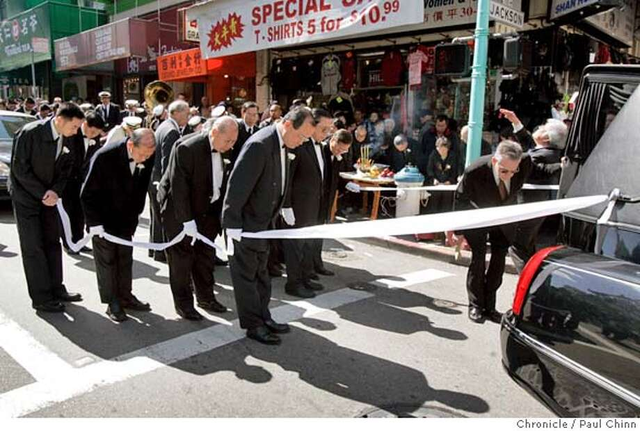 Pallbearers bow after a stop for an offering from a local business on Grant Avenue. A funeral procession for Allen Leung makes its way through the streets of Chinatown. Photo: PAUL CHINN