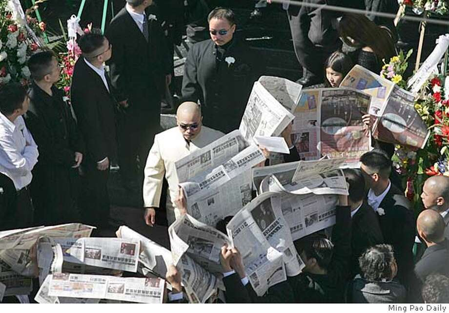 "Raymond ""Shrimp Boy"" Chow, in a white suit, attends the funeral of slain Chinatown leader Allen Leung. Mourners are holding up newspapers to block photographers. Photo: Ming Pao Daily"