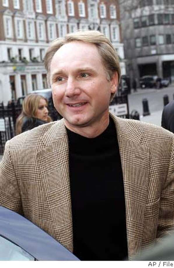 """** FILE ** Dan Brown, author of the book 'The Da Vinci Code', arrives at the Royal Court of Justice in London for a legal case taken out against him by authors Michael Baigent and Richard Leigh, in a Monday Feb. 27, 2006 photo. Brown, best-selling author of """"The Da Vinci Code,"""" is working to put up a wrought-iron fence around his home to keep out uninvited guests. It would sit atop a 2-foot-high stone wall and rise up no more than 6 feet, according to a letter his attorney presented to Rye selectmen recently. (AP Photo) Photo: File"""